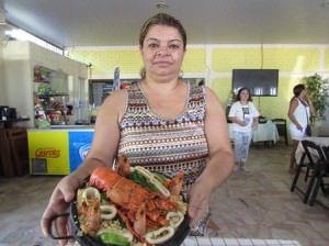 A empresária Gleici Simone, do Recanto de Manguinhos, mostra o prato Arroz de Marisco a Baronesa que participa do festival