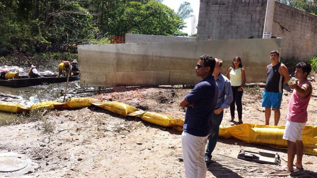 Moradores observam a retirada do óleo. No muro, a marca de onde a água oleosa chegou. Foto: Bruno Lyra