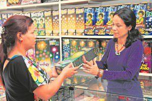 Maria Aparecida, da Arte Fogos, orienta cliente para o uso dos fogos de artifício que viram febre em tempos de festas juninas. Foto: Edson Reis