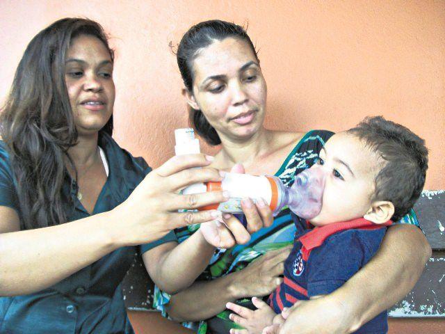 A mãe Kelly Pereira e a tia Keila seguram o pequeno Miguel para aplicar bombinha por conta de bronquite asmática. Foto: Bruno Lyra